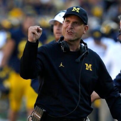 Michigan football coach Jim Harbaugh encourages his