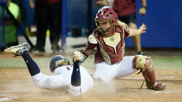 Auburn outfielder Morgan Podany, left, scores the game
