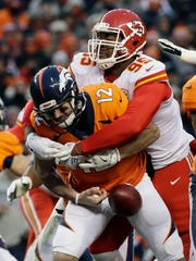 Denver Broncos quarterback Paxton Lynch (12) fumbles as he is tackled by Kansas City Chiefs defensive end Chris Jones (95) during the second half of an NFL football game Sunday, Dec. 31, 2017, in Denver. Chiefs inside linebacker Ramik Wilson picked up the fumble and score on the play.