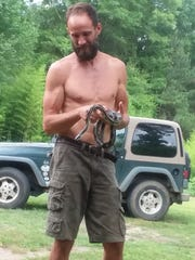 Joseph Hosey of Laurel holds a rat snake he found during