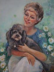 A painting of Margery Gilmore with her dog Pepe that was buried in the Stanton SPCA cemetery.