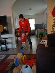 Amanda Lofland helps guides her 11-month-old son Braylen along as he starts the beginning stages of attempting to walk.