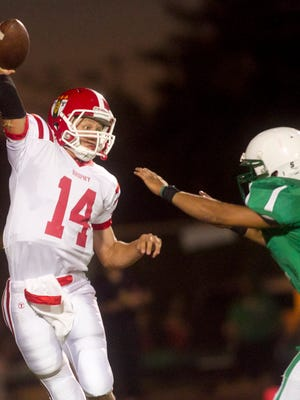 Brophy Prep quarterback Tyler Bruggman gets rid of the ball as he is pressured by St. Mary's defensive lineman Jose Serna  during the 2010 high school football game at Phoenix College in Phoenix. The two schools haven't played since 2013.