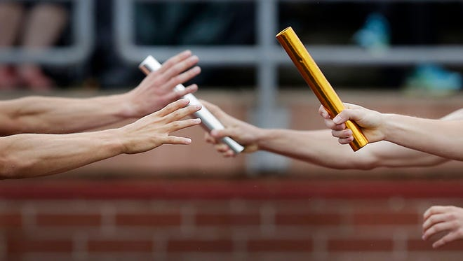 Batons are passed in the boys 4x800 relay at the 2015 MHSAA Track & Field Finals  Division 1 at Rockford High School on Saturday, May30, 2015.