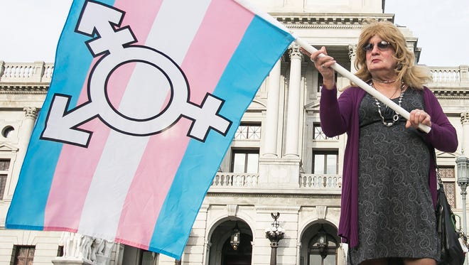 In this file photo, Ellen Davidson, of Elizabethtown, holds the transgender flag Thursday, March 31, 2016,  during a rally at the state Capitol to fight for the passage of the Fairness Act which would offer protections for LGBT individuals with regards to employment and housing. Amanda J. Cain photo
