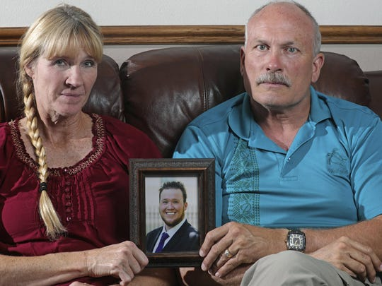 In this Monday, Sept. 9, 2019, photo, Rod and Tonya Meldrum hold a portrait of their son Devin Meldrum, in Provo, Utah. He suffered from debilitating cluster headaches and fatally overdosed after taking a single fentanyl-laced counterfeit oxycodone pill purchased from a dark-web store run by Aaron Shamo, according to his family and authorities. Shamo was not charged in Meldrum's death, and his lawyers have argued that and other alleged overdoses can't be definitively linked to him. (AP Photo/Rick Bowmer)