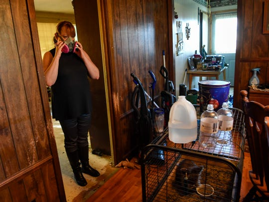 Maria McClure wears a gas mask as she cleans out her father's home in Clarksville, Tenn., on Monday, Oct. 9, 2017. The home is in foreclosure and is permeated with putrid smells of dog feces, urine and years of cigarette smoke.