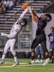 Dinuba's Josh Huerta, left, deflects pass intended