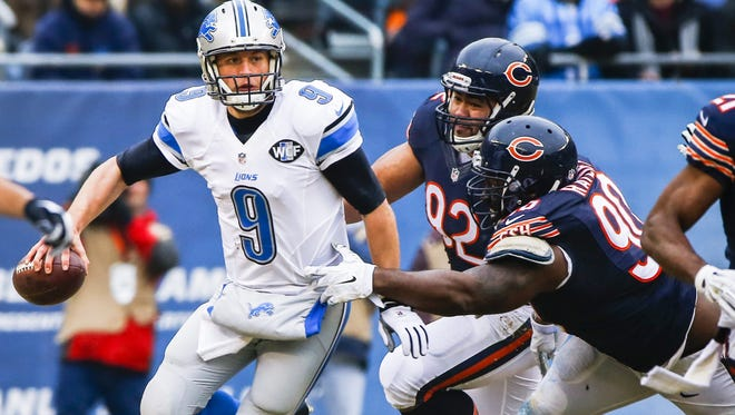 Lions quarterback Matthew Stafford  is pressured by Chicago Bears' Stephen Paea and Jeremiah Ratliff (R) in the first half.