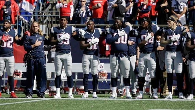 New England Patriots players and coaches stand during the national anthem in an undated photo.