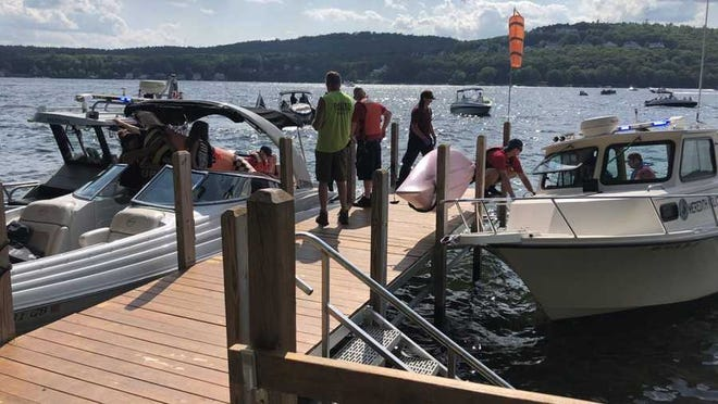 First responders meet Stoneham, Massachusetts, police officer Joe Ponzo at a dock after he helped save a pilot who crashed his plane into Lake Winnipesaukee in New Hampshire on Sunday, Aug. 9, 2020.