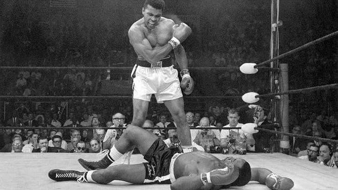Muhammad Ali stands over Sonny Liston after knocking him out in a heavyweight title fight.