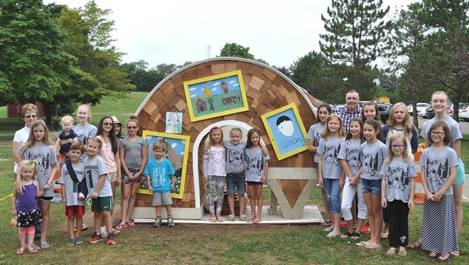 Members of the Friends Club pose with their Free Little Library in McHattie Park.