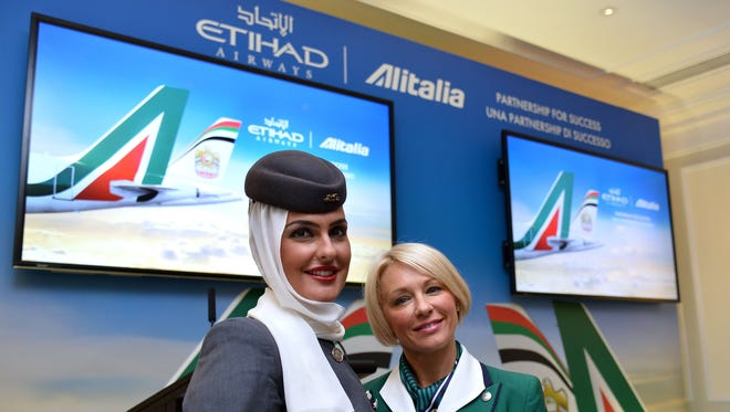 Alitalia and Etihad attendants pose during a press conference in Rome on Aug. 8, 2014.