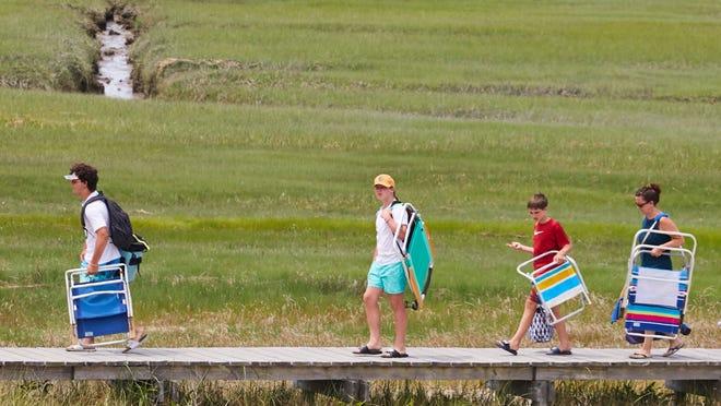 Family and friends set off to Town Neck Beach in Sandwich across the Sandwich Boardwalk.