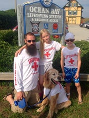 Molson, newly trained as a lifeguard, poses with his