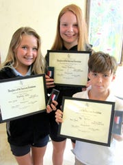 Students, from left,  Stephanie Carter (8th grade), Alonna Anderson (7th grade) and Kai Spitzer (6th grade) show the certificates the Marco DAR awarded them for their entries in the DAR American History essay contest.