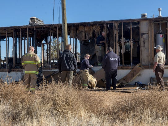 Officials investigate what remains of a trailer that was engulfed in smoke and flames by the time firefighters arrived on the scene Wednesday evening in Kirtland. Two children died in the blaze.