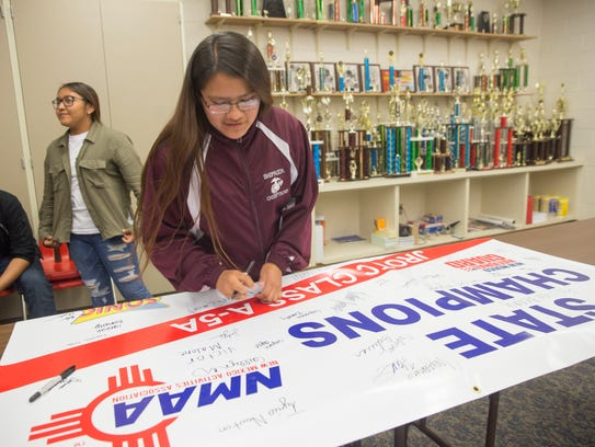 Shiprock Marine Corps Junior ROTC student Caitlyn Nez signs her team's New Mexico Activities Association 5A-State Championship banner on Monday at Shiprock High School.