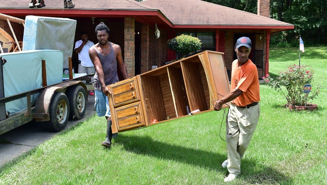 Brandon Scott, left, helps Dexter Smith move furniture out of his home Thursday in Crosby, Miss. Flooding damaged numerous homes and displaced nearly half the town's population.