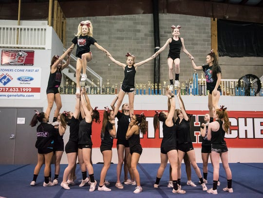 The Black Onyx cheer team form a pyramid during a practice