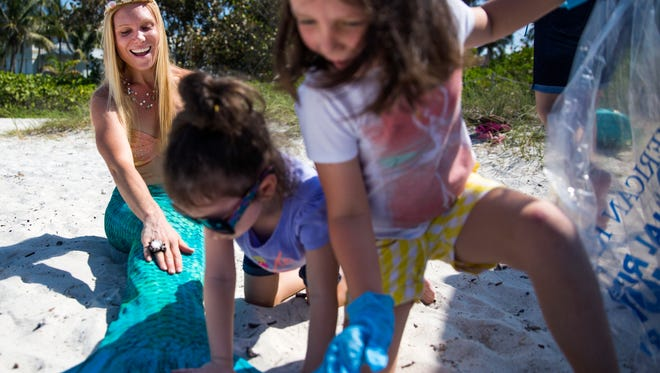 "Sisters Tori, 5, and Zoey Martin 4, play with Shelley ""Sea Shelley"" McKernan's mermaid tail during the second annual Naples Pier Collier County Waterkeeper Beach Cleanup on Saturday, April 1, 2017, in Naples. McKernan is using her sparkly mermaid tail to teach people about the environment, health and other issues she's passionate about."