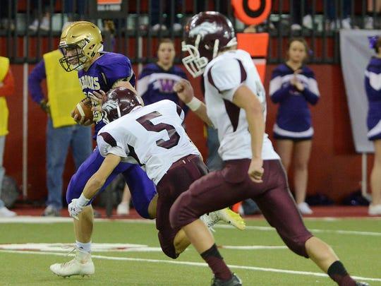 Winner's Kayleb Brozik carries the ball down the field past Tri-Valley's Brock Newman in Friday's class 11B football championship at the DakotaDome in Vermillion, Nov 13, 2015. Winner beat Tri-Valley 45-6.