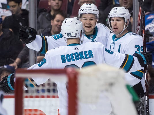 San Jose Sharks' Tomas Hertl, back left, of the Czech Republic; Logan Couture, right; and Mikkel Boedker, of Denmark, celebrate Couture's goal against the Vancouver Canucks during the first period of an NHL hockey game Saturday, March 17, 2018, in Vancouver, British Columbia. (Darryl Dyck/The Canadian Press via AP)