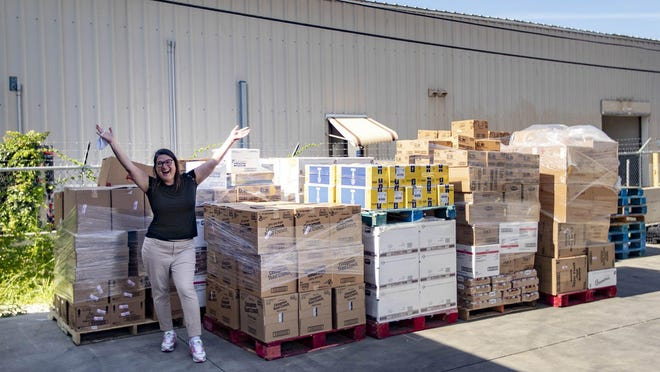Karen Erren, executive director of the Palm Beach County Food Bank, celebrates a large food donation paid for by four Palm Beach families Thursday in Lantana. The truck deliveries will continue until state and local economies start to stabilize, at least through May.