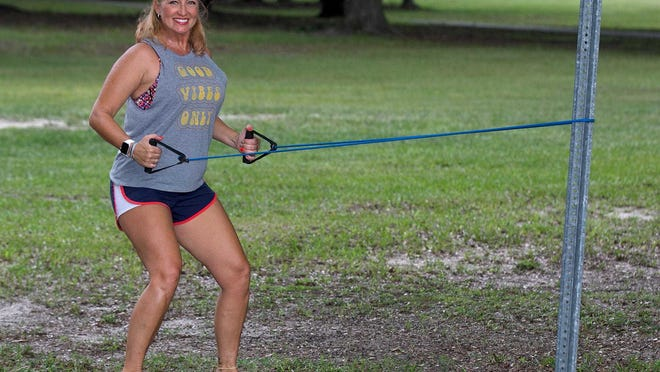 Marlo Alleva demonstrates a standing row with a resistance band.