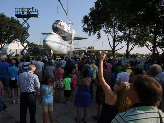 Spectators look on as a space shuttle replica is placed atop the Shuttle Carrier Aircraft (SCA) Thursday morning, Aug. 14, 2014, at NASA?s Johnson Space Center  in Houston. The old Boeing 747 formerly transported shuttles piggyback to Florida following flights. Visitors will be allowed to enter both vehicles when the permanent exhibit opens in 2015. (AP Photo/Conroe Courier, Kar B Hlava)