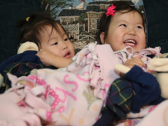 Erienne Tilzey, right, and Nora, both 2, were adopted from Chinese orphanages this summer by a Key Peninsula family. Nora has a serious heart condition; Erienne was born with a life-threatening intestinal condition.