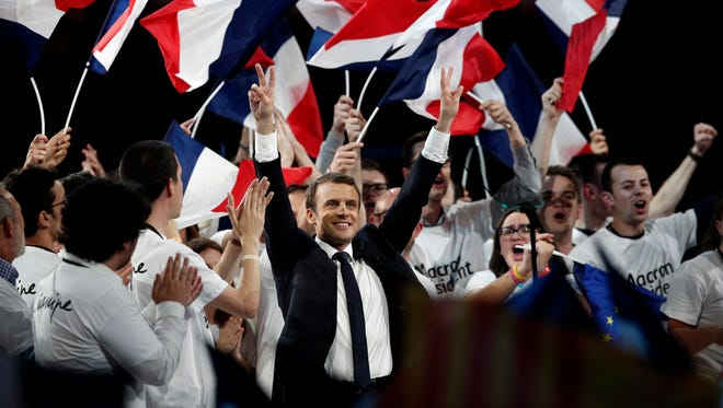 Emmanuel Macron, French presidential election candidate from the centrist 'En Marche!' (Onward!) political party, gestures toward the audience after making a speech during his a rally in Paris on April 17, 2017.
