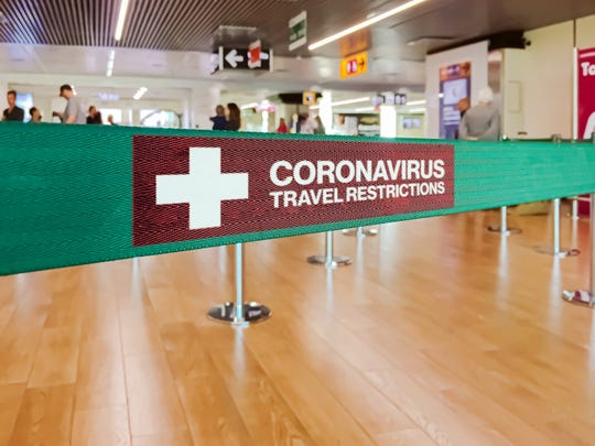 """""""Coronavirus Travel Restrictions"""" on a barrier at an airport"""