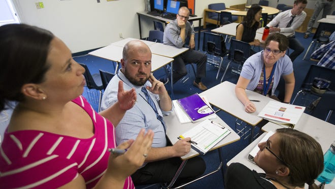 Natalie Naranjo (left) discusses scenarios with teachers Cory Nelson (center), Megan Hamontree (top) and Cara Narbone during a professional development program for first and second year teachers at Mensendick Elementary School on October 19, 2015. The Sanford Inspire Program has veteran teachers coach younger teachers to provide guidance and support.