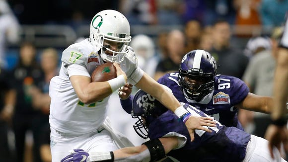 Jan 2, 2016; San Antonio, TX, USA; Oregon Ducks quarterback Jeff Lockie (17) is tackled by Texas Christian Frogs linebacker Ty Summers (42) at the Valero Alamo Bowl in the Alamodome. TCU won 47-41 in overtime. Mandatory Credit: Erich Schlegel-USA TODAY Sports