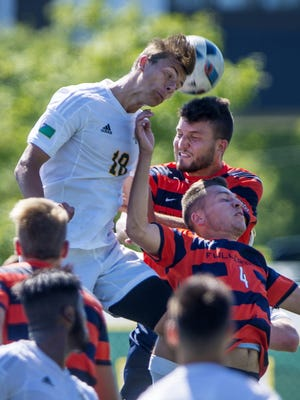 The University of Vermont's Arnar Steinn Hansson, left, heads a corner kick against Cal State Fullerton's Alex Heilmann and Corentin Ohlmann in Burlington on Friday, August 26, 2016.