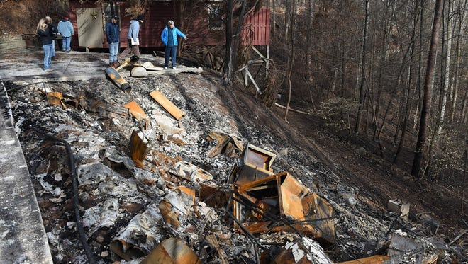 Sue Thompson, right, works with volunteers at her burned home in Gatlinburg.