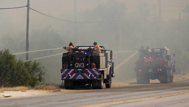 Quail Valley VFD firefighters suppress a brush fire as it approached Armstrong Street July 29, 2017.