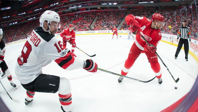 Red Wings defenseman Niklas Kronwall and Devils right wing Drew Stafford battle for the puck Saturday.