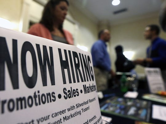 A sign attracts job-seekers during a job fair at the