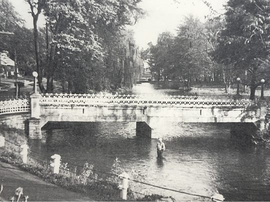 A photograph from bygone days shows the bridge from the village of Scotland to the Scotland School for Veterans Children and a brush-free stream bank.