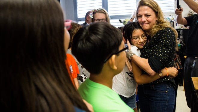 Hope Cliff hugs one of her fifth-grade students after receiving a Golden Apple award at Sea Gate Elementary in Naples on Friday, Feb. 23, 2018. The Golden Apple awards highlight best practices in teaching and were presented to five teachers in Collier County.