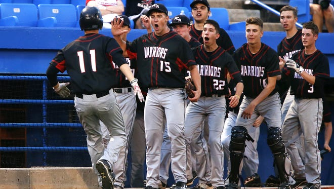New Covenant Academy first baseman Josh Isbell (11) is greeted by teammate Cody Malan (15) and the rest of the Warriors after scoring on a balk during a 2016 playoff game. Isbell and Malan were both named first team all-state by the Missouri High School Baseball Coaches Association