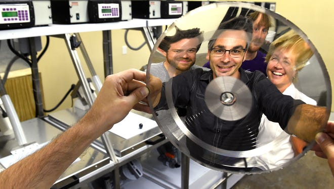 Welcome to 1979 studios and production owner Chris Mara, center, is a little distorted as he's reflected in an electroplate stamper with his team — Cameron Henry, Dan Emery and partner Lori Hines — but the goal of the new facility is to reduce distortion when vinyl records are produced.