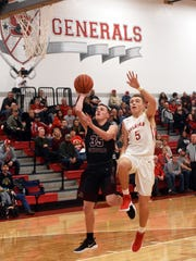 Parker Zachrich goes up for a layup over Sheridan's Dylan Emmert during the Muskies' 65-39 win on Friday night at Glen Hursey Gymnasium.