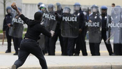 A man throws a brick at police Monday, April 27, 2015, following the funeral of Freddie Gray in Baltimore. Gray died from spinal injuries about a week after he was arrested and transported in a Baltimore Police Department van.