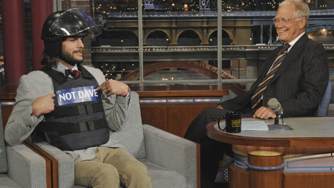 "In this photo provided by CBS, ""Two and a Half Men"" star Ashton Kutcher, left, pokes fun at host David Letterman by wearing a helmet and bullet proof vest labeled ""Not Dave"" on the set of the ""Late Show with David Letterman"" Wednesday, Aug. 24, 201,1 in New York."