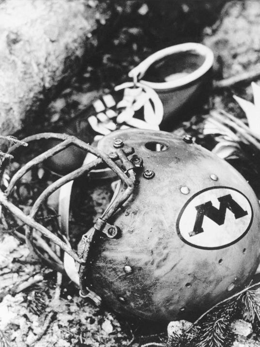 FILE - In this Oct. 3, 1970, file photo, a charred Wichita State University football helmet is shown amid the wreckage of a plane that crashed in Silver Plume, Colo. Six weeks later, on Nov. 14, 1970, a plane carrying members of the Marshall football team crashed. As fate would have it, Marshall's first trip to the NCAA Tournament in 31 years means a date with Wichita State on Friday, March 16, 2018, in San Diego. (AP Photo/File)