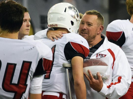 Coach Chad Garrow greets his players following a loss to Sioux Falls Washington in the 2016 state football finals.